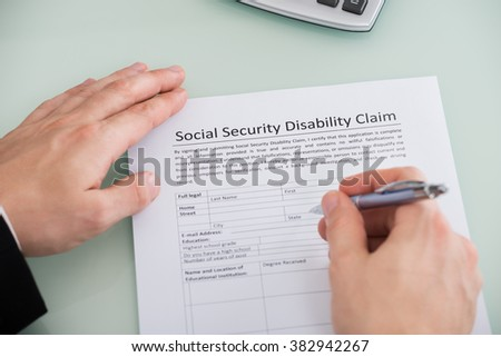 Close-up Of Person Hand Over Social Security Disability Claim Form - stock photo