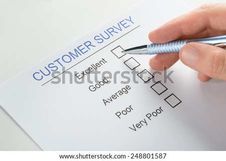 Close-up Of Person Hand With Pen Over Blank Customer Survey Form - stock photo