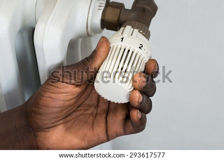 Close-up Of Person Hands Adjusting Thermostat Radiator Valve - stock photo