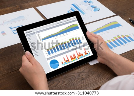 Close-up Of Person Hands Analyzing Financial Statistics Displayed On Digital Tablet - stock photo