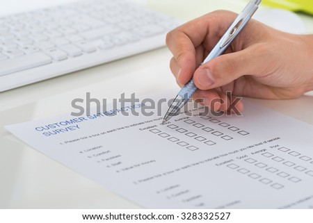 Close-up Of Person Hands Filling Survey Form With Pen - stock photo