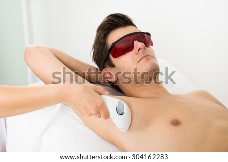 Close-up Of Person Hands Giving Laser Epilation Therapy To Young Man - stock photo