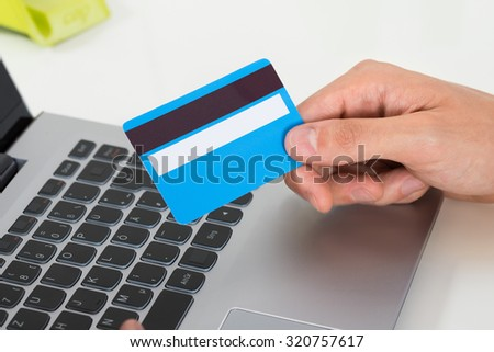 Close-up Of Person Hands Holding Credit Card Over Laptop Keypad - stock photo