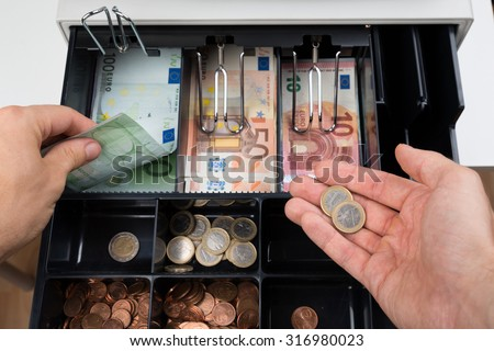 Close-up Of Person Hands With Money Over Cash Register - stock photo