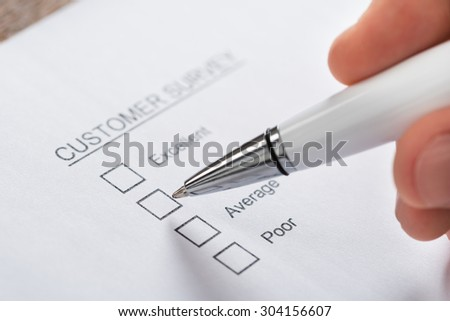 Close-up Of Person Hands With Pen Filling Customer Survey Blank Form - stock photo