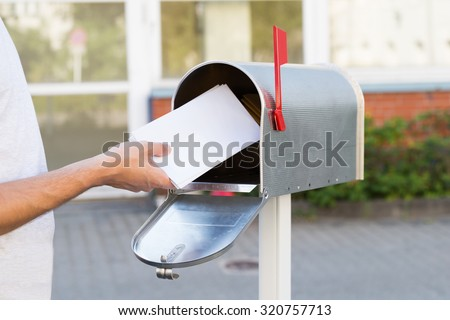 Close-up Of Person Putting Stack Of Letters In Mailbox - stock photo
