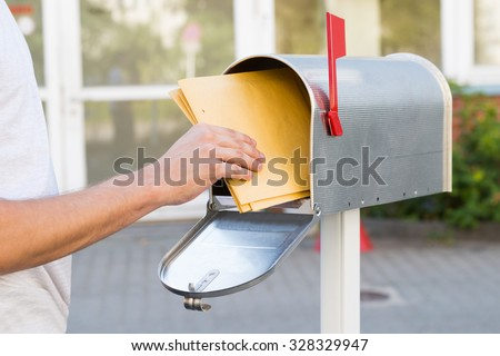 Close-up Of Person Removing Yellow Letters From Mailbox - stock photo