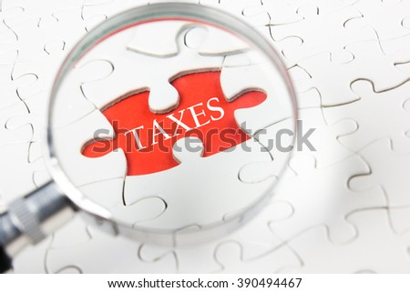 Close-up Of Person's Hand Holding Magnifying Glass Over TaxesText - stock photo