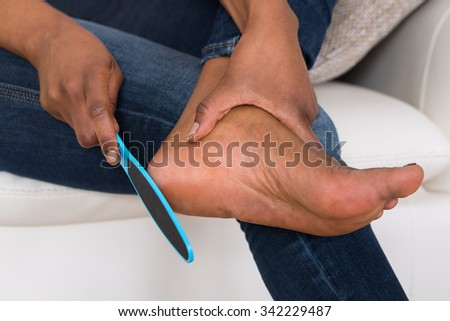 Close-up Of Person's Hand Pedicuring Her Legs - stock photo