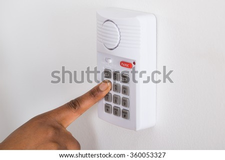 Close-up Of Person's Hand Pressing Button On Security System - stock photo