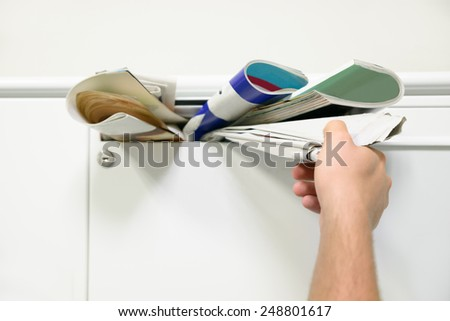 Close-up Of Person's Hand Taking Documents From Mailbox - stock photo