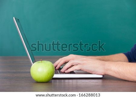 Close-up Of Person's Hand Using Laptop With Green Apple On Desk - stock photo