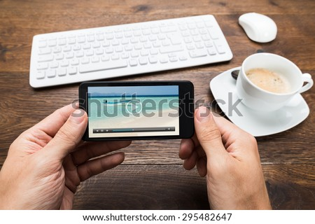 Close-up Of Person Watching Video On Mobile Phone With Cup Of Tea At Desk - stock photo