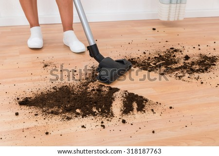 Close-up Of Person With Vacuum Cleaner Cleaning Dirt On Floor - stock photo