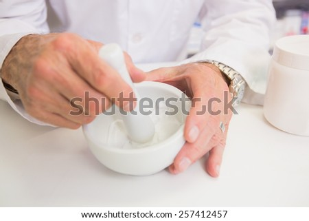 Close up of pharmacist mixing medicine in the pharmacy - stock photo