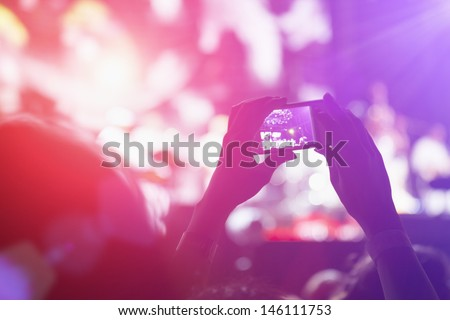 Close up of photographing with smartphone during a concert - stock photo