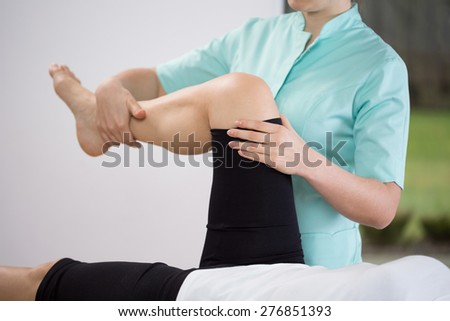 Close-up of physiotherapist doing exercise of lower limb - stock photo