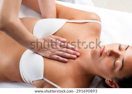 Close up of physiotherapist doing manipulative massage on young woman chest. - stock photo
