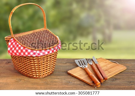 Close-up Of Picnic Bench With Hamper And BBQ Grill Tools And Summer Garden With Sunbeams In The Background - stock photo