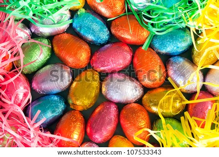 Close-up of pile of colorful chocolate Easter Eggs surrounded by colorful grasses. - stock photo