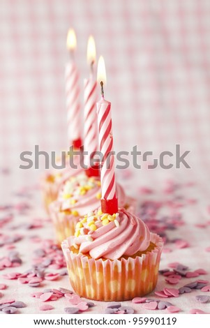 Close-up of pink muffins with party candles. Studio shot. - stock photo