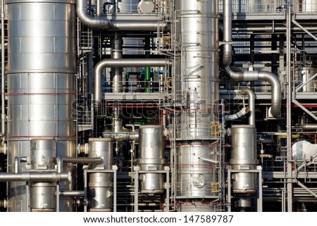 Close-up of pipelines and destillation tanks of an oil-refinery plant - stock photo