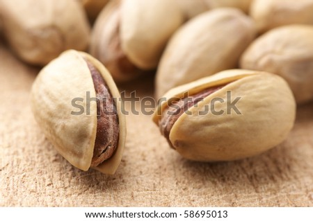 Close-up of pistachio on wooden surface. Selective focus on foreground. - stock photo