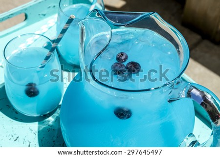 Close up of pitcher and cocktail glasses filled with blueberry lemonade with flavored vodka, fresh blueberries and ice - stock photo