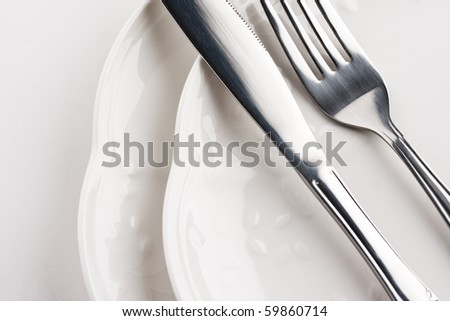 Close up of place setting with white plates, fork and knife. - stock photo