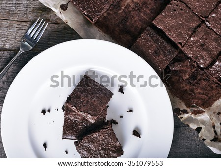 Close up of plate with stack of delicious and soft, square sliced chocolate brownies and extra brownies at the pan behind it. Top view image with dark vintage wood background. - stock photo