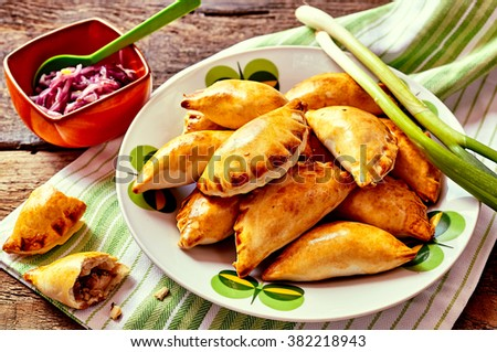 Close Up of Plateful of Fresh Baked Empanada Pastries with Fresh Green Onions and Cabbage Side Dish Served on Rustic Wooden Table with Copy Space - stock photo
