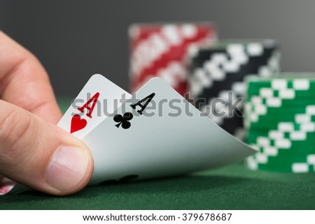 Close-up Of Poker Player Lifting Two Cards - stock photo