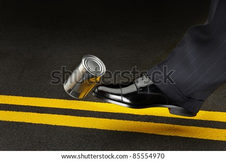 close up of politician's shoe kicking a dented shiny can down the road - stock photo
