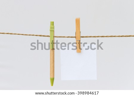 close up of post it reminders and clothespins attached to a rope on white background with clipping path - stock photo