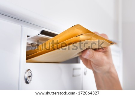 Close-up Of Postman Putting Letters In Mailbox - stock photo