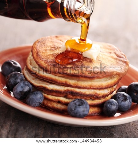 Close-up of pouring maple syrup on stack of pancakes. - stock photo