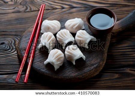 Close-up of prawn dim-sum dumplings in a rustic wooden setting - stock photo