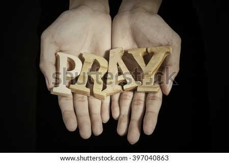 Close up of prayer hands showing a word of pray in dark background - stock photo