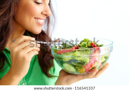 Close-up of pretty girl eating fresh vegetable salad - stock photo
