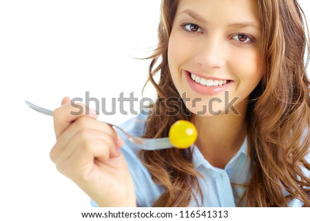 Close-up of pretty girl holding fork with fresh cherry tomato - stock photo