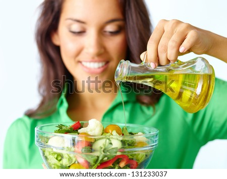 Close-up of pretty girl pouring oil into vegetable salad in glass bowl - stock photo