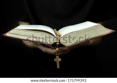Close up of priest reading the holy bible with rosary - stock photo