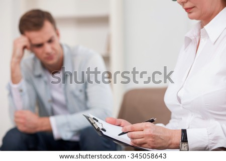 Close up of professional advisor is sitting in her office and listening attentively to a man. The guy has stress. The woman is writing. Focus on folder of documents in her hands - stock photo
