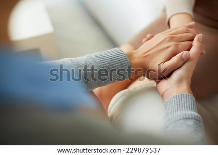 Close-up of psychiatrist hands together holding palm of her patient - stock photo