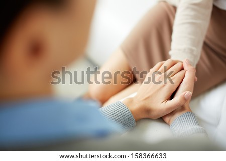 Close-up of psychiatrist keeping her hands together while listening to her patient - stock photo
