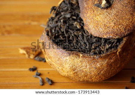 Close-up of pu-erh tea aged in tangerine on bamboo background. - stock photo