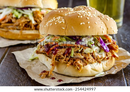 Close up of pulled pork barbeque sandwich with coleslaw sitting on wooden table with glass of beer - stock photo