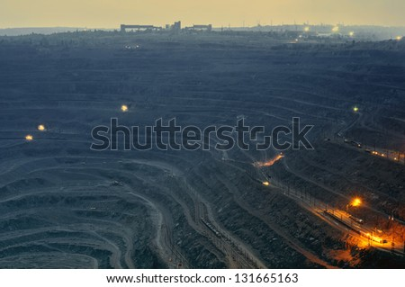 close up of quarry extracting iron ore with heavy trucks, excavators, diggers and locomotives at night - stock photo