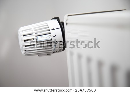 Close up of radiator thermostat, selective focus, white background - stock photo
