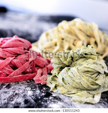 Close up of raw home hand made fresh pasta with variety of flavours, beetroot, herb, spinach - stock photo
